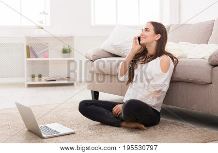 Young woman using a laptop and mobile. Sitting on the floor and making a pleasant call