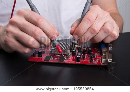 Electronic circuit red board inspecting close up. Engineer measuring computer component, maintenance support and repairing service concept.