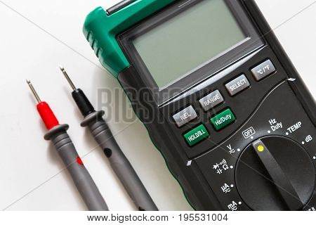 Digital multimeter with switch and probes. Measurement electrician tool closeup on white background