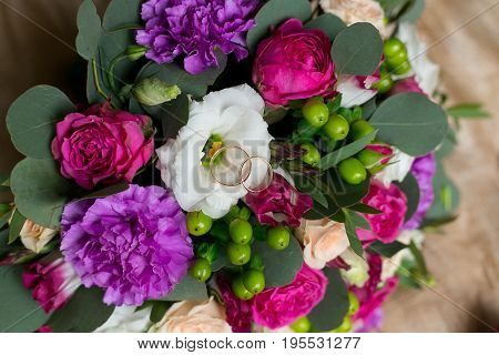 wedding bouquet of peonies with wedding rings.