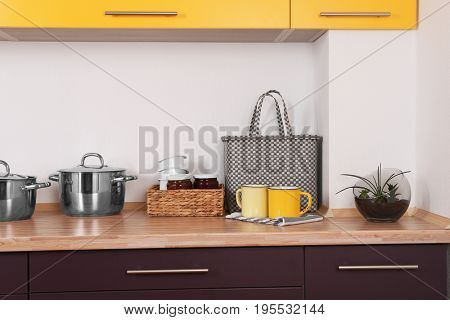 Composition with mugs, bag and plant on counter in kitchen