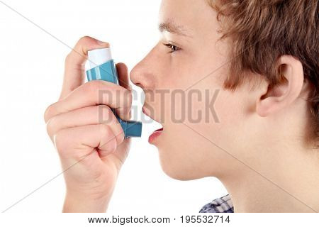 Young boy using inhaler for asthma and respiratory diseases on white background