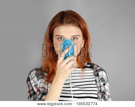 Young woman using nebulizer for asthma and respiratory diseases on light background