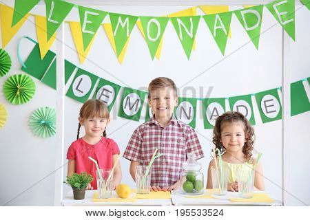 Cute little kids selling lemonade at counter