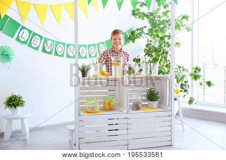 Cute little boy selling lemonade at counter