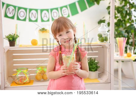 Cute little girl holding glass and blurred stand with lemonade on  background