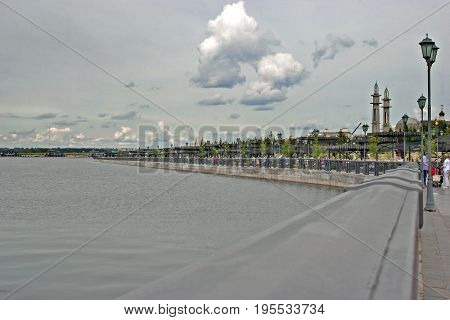 the city quay on the river on background sky with clouds people walk along promenade