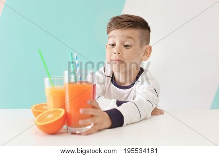 Cute little boy making long arm for glass of juice while sitting at table, on color background