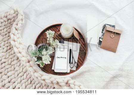 Top view of wooden tray with smartphone, old photos, candle and spring flowers on white bedding. Relaxing and posting to blog in bed at home.