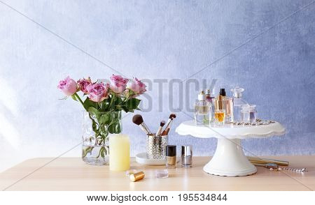 Stand with bottles of perfume on table