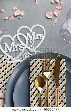 Beautiful table setting for lesbian wedding on gray background