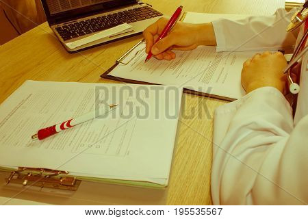 Medicine doctor's working table. Healthcare and medical concept. Female medical doctor writing something sitting at her office - Retro color