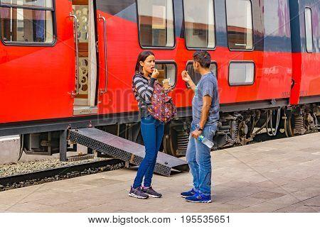 GUAYAS, ECUADOR, OCTOBER - 2016 - Young couple eating snack while waiting at train station in Guayas district Ecuador