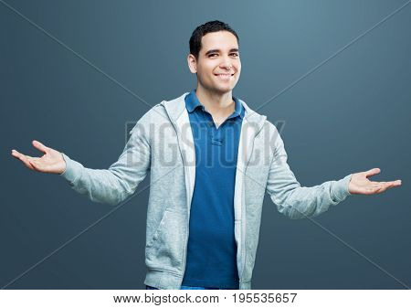 young handsome smiling man with arms wide spread isolated against gray background