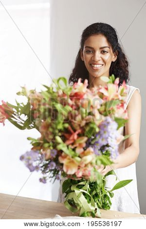 Portrait of beautiful african girl smiling looking at camera holding bouquet of alstroemerias. Copy space.