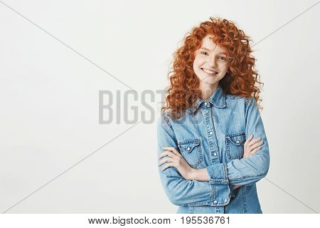 Pretty happy cheerful redhead girl with flyingcurly hair smiling laughing looking at camera over white background.