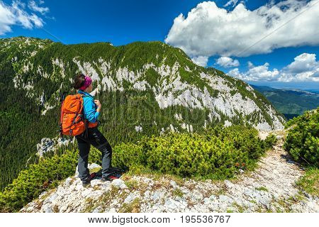 Hiker woman with backpack and mountain equipment looking at view in Piatra Craiului mountains Carpathians Transylvania Romania Europe