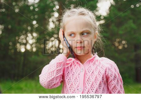 Kid with smartphone. Closeup portrait of pretty smiling funny girl kid holding cell phone talking to her mom, dad family isolated green trees outdoors summer background. Kids and technology concept