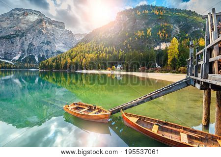 Breathtaking autumn landscape spectacular old wooden dock house on the lake with typical wooden boats Braies lake Dolomites Italy Europe