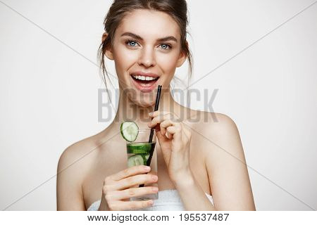 Young beautiful girl with perfect clean skin smiling looking at camera holding glass of water with cucumber slices over white background. Healthy nutrition. Copy space.