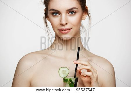 Young beautiful naked girl with perfect clean skin smiling looking at camera holding glass of water with cucumber slices over white background. Facial treatment. Copy space.