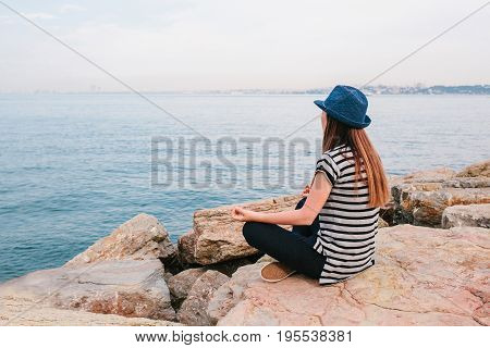 Young beautiful girl in a hat practicing yoga and meditating on stones next to the sea. Recreation. Relaxation.