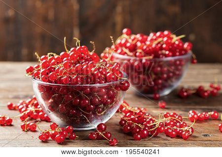 Red currant in a glass plate on a wooden background cooking a healthy dish of red currant space for text