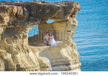 beautiful gorgeous bride and stylish groom on rocks, on the background of a sea, wedding ceremony on cyprus.