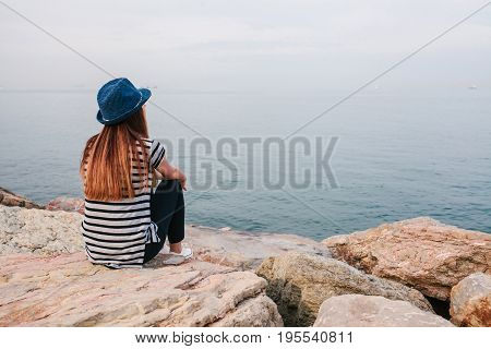 Young beautiful girl in a hat sits on the rocks on the seashore and looks into the distance. Vacation, relaxation.
