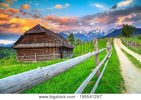 Stunning summer alpine landscape with green fields and high snowy mountains Bran Transylvania Romania Europe