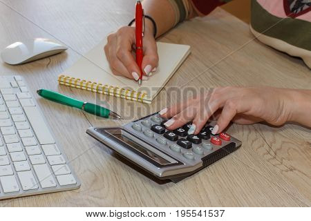 Close up view of bookkeeper or financial inspector hands making report calculating or checking balance. Business plan with money calculator and pen on the table