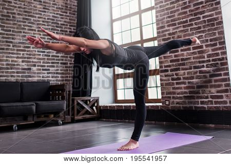 Fit woman doing warrior three yoga pose standing on one leg leaning forward with chest and leg parallel to the floor working out in modern gym.