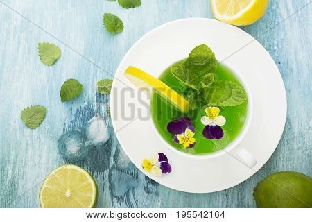 Cold refreshing drink with mint syrup, ice cubes, mint, lemon, edible flowers of a garden viola on a light turquoise summer background in a white ceramic cup. Selective focus. Top View