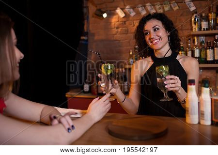 Pretty smiling female bartender offering drinks to guests standing behind bar counter.