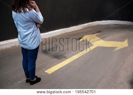 Young woman standing in front of two roads. Difficulties in choosing.