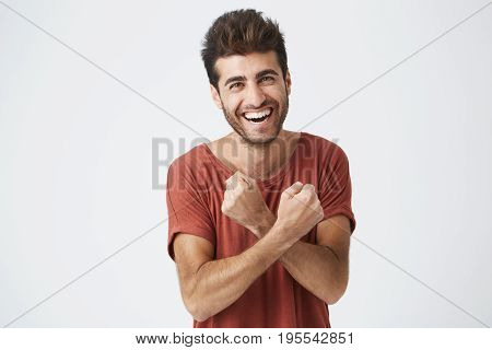 Handsome young sun-tanned man feeling excited, gesturing actively, keeping fists clenched and crossed, joyfully laughing, happy with good luck. Student excited by successful passing of exams.