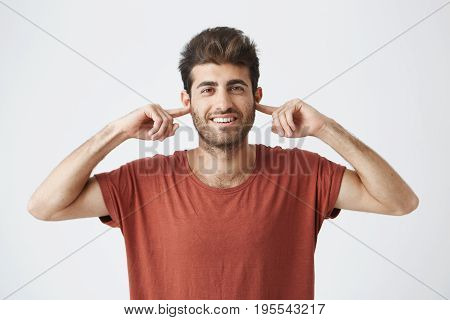 Portrait of annoyed young male Caucasian with eyes closed plugging his ears with fingers can't stand loud noise or ignoring stressful unpleasant situation or conflict. Negative human emotions.
