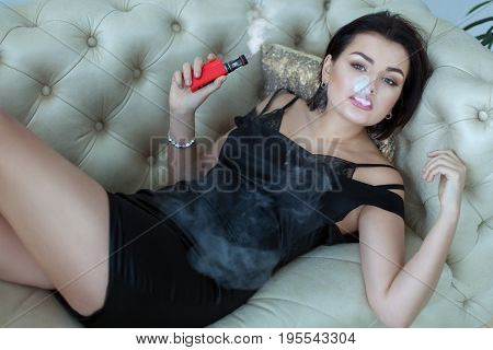 Woman lying on the sofa smoking an electronic cigarette and exhaling steam.