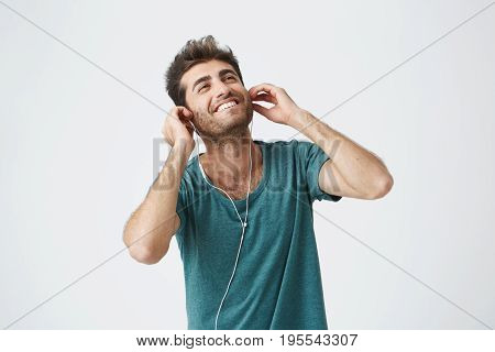 Young sun-tanned smiling hipster enjoying good tracks using free music app on gadget. Studio shot of good-looking full of joy bearded man.