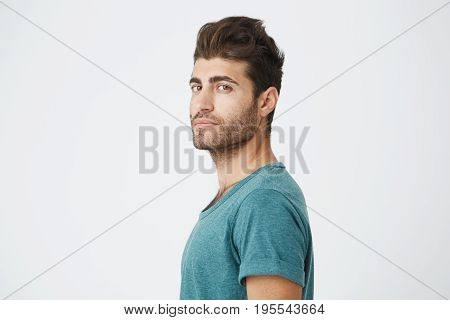 Stylish bearded man with appealing dark eyes seriously looking into camera. Handsome hipster guy with trendy hairstyle and beard on white background.