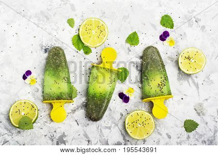 Homemade vegetarian ice creampopsicle fruit citrus peppermint juice with chia seeds is decorated with edible flowers of garden violas in trendy colors. Top view. The concept of a healthy diet