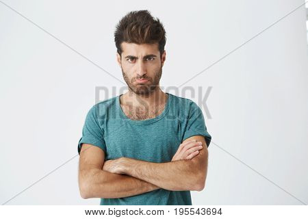 Studio shot of angry grumpy young male dressed casually keeping arms folded, looking at camera with strict and skeptical expression, doesn't believe excuses of his unfaithful girlfriend.