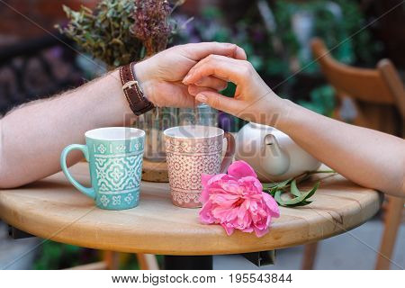 Man holds a woman's hand while sitting at a table in a street cafe. Romantic date. Natural