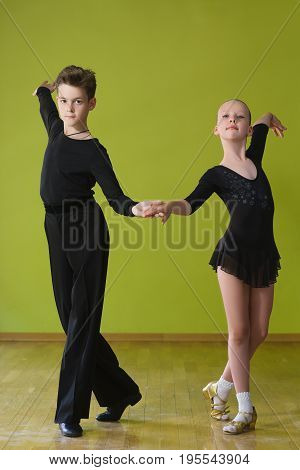 Boy and girl dancing ballroom dance in classroom