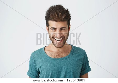Attractive and cheerful young man with beard and stylish haircut wearing blue t-shirt blinking his eyes with pleasure having happy expression. Facial expressions and people emotions concept.