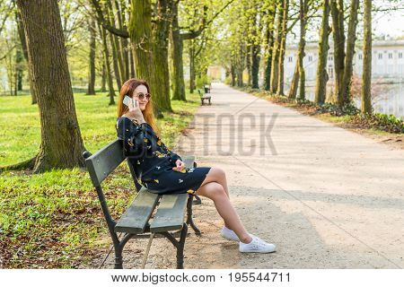 Side view portrait, young, happy beautiful woman sitting on bench and speaking on cell phone. Sitting on park bench. Outdoors background.