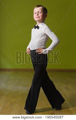 Little cute boy dancing ballroom dance in classroom