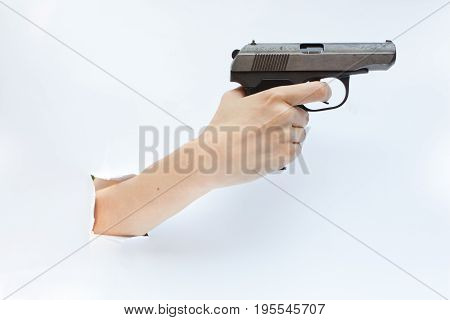 Hand with a pistol protrudes from a hole in a white background