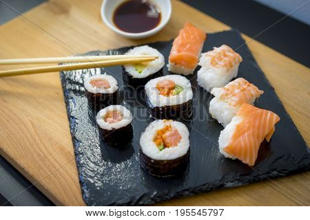 Asian food, Sushi on a wooden table on black slate plate with soy sauce and chopsticks