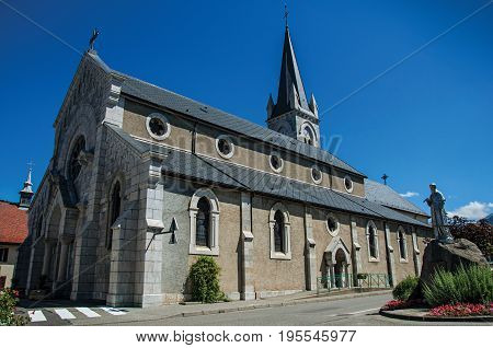 Church and sculpture in the village of Thorens-Glières, with blue and sunny sky. Located in the department of Haute-Savoie, Auvergne-Rhône-Alpes region, in south-eastern France